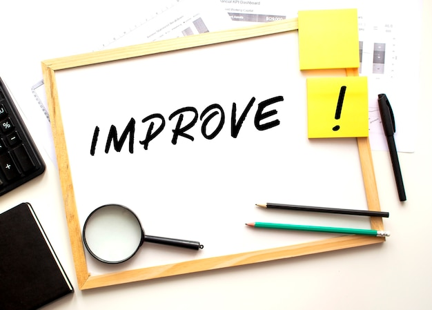O texto de melhorar é escrito em um quadro branco. mesa de trabalho com material de escritório. conceito de negócios e financeiro.