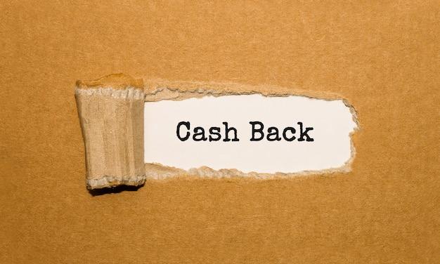 O texto dinheiro de volta aparecendo atrás de papel marrom rasgado