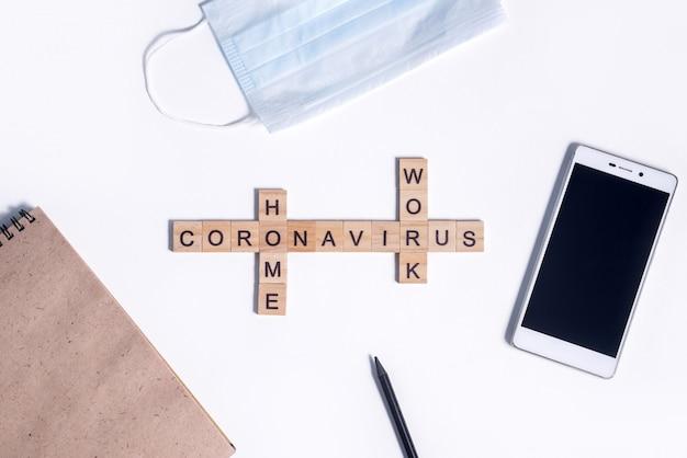 O texto do coronavírus de letras de madeira funciona em casa. material de escritório, calculadora, bloco de notas de papel, telefone, lápis e máscara médica protetora na área de trabalho.