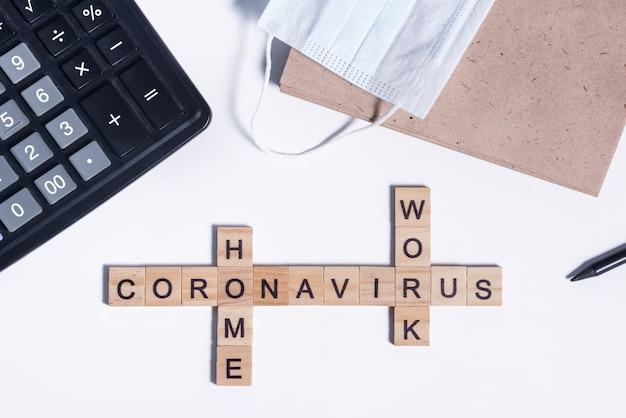 O texto do coronavírus de letras de madeira funciona em casa. material de escritório, calculadora, bloco de notas em papel para anotações, lápis e máscara médica protetora na área de trabalho.