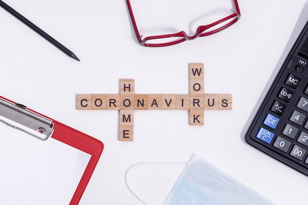 O texto do coronavírus de letras de madeira funciona em casa. material de escritório, calculadora, tablet, óculos, lápis e máscara protetora médica na área de trabalho.