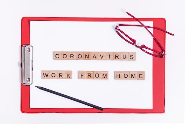 O texto do coronavírus de letras de madeira funciona em casa. material de escritório, um tablet vermelho, lápis e óculos na área de trabalho. trabalhando durante uma pandemia de vírus.