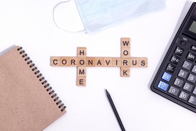 O texto do coronavírus de letras de madeira funciona em casa. material de escritório, uma calculadora, bloco de notas em papel para anotações, um lápis e uma máscara médica protetora na área de trabalho.