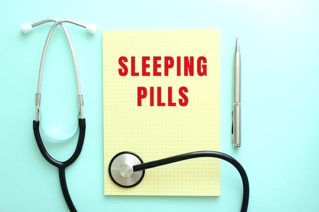 O texto em vermelho pílulas para dormir está escrito em um bloco amarelo que fica ao lado do estetoscópio sobre um fundo azul.