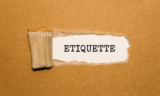 O texto etiquette aparecendo atrás de um papel pardo rasgado