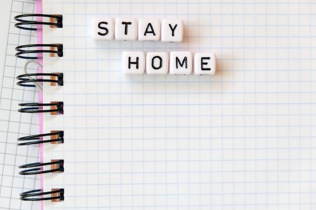 O texto fica em casa, palavra feita de letras cúbicas em um fundo de bloco de notas de papel branco