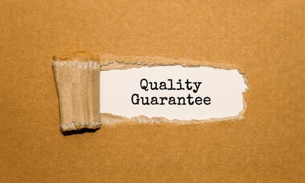 O texto garantia de qualidade aparecendo atrás do papel pardo rasgado