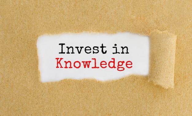 O texto invest in knowledge aparecendo por trás de um papel pardo rasgado.