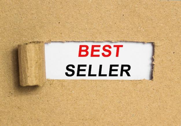 O texto mais vendido por trás do papel pardo rasgado. imagem do conceito de negócio