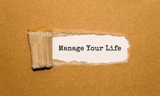 O texto manage your life aparecendo atrás de um papel marrom rasgado