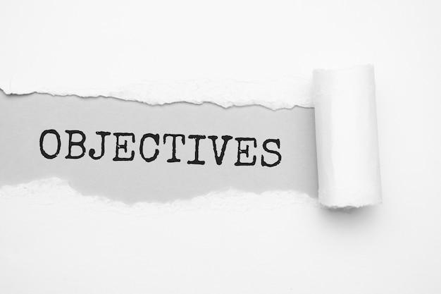 O texto objetivos aparecendo atrás de papel pardo rasgado