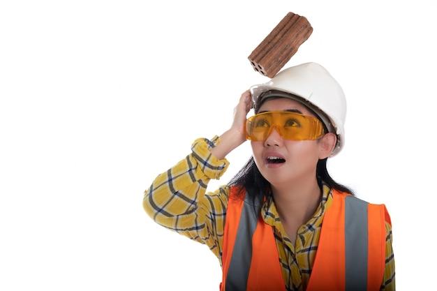 O tijolo do bloco de madeira caiu na cabeça da jovem engenheira asiática sobre o trabalhador de capacete