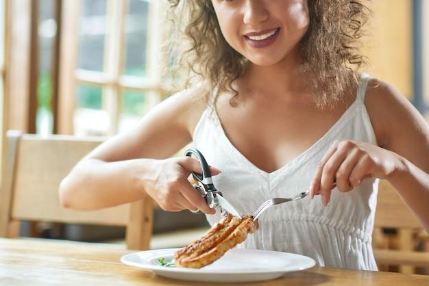 O tiro colhido de uma mulher feliz que sorri alegremente almoçando no restaurante que corta a carne grelhada com tesoura sorri a positividade que come o conceito do estilo de vida do prazer.