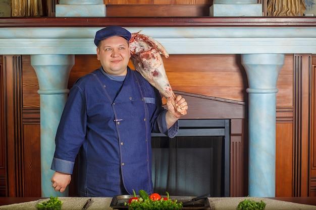 O tiro da metade legth do cozinheiro chefe masculino pensativo, prende a parte crua vermelha muito grande de carne.