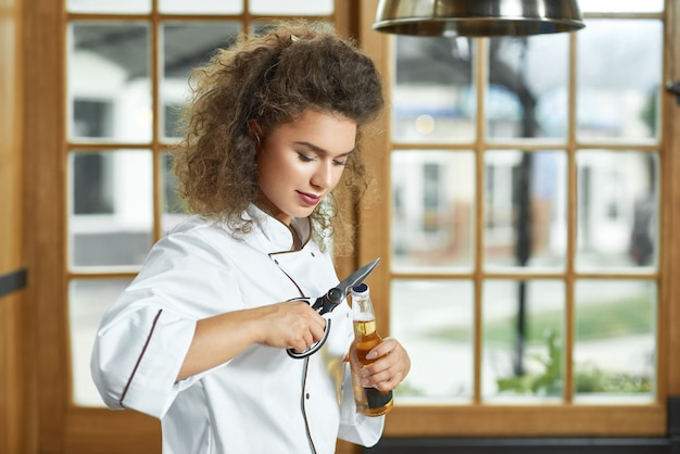 O tiro de um cozinheiro chefe fêmea bonito que abre uma garrafa de cerveja no relaxamento da bebida do álcool da ocupação da profissão da copyspace da cozinha relaxa o conceito da bebida.
