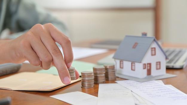O tiro do close-up da casa modelo e a mão são moedas arranjadas, conceitos de compra da casa.