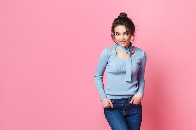 O tiro do estúdio da mulher louro nova feliz vestiu-se ocasionalmente calças de brim e blusa azul. fundo rosa copie o espaço