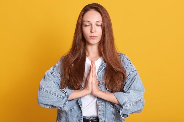 O tiro interno da fêmea europeia atrativa vestiu-se no revestimento da sarja de nimes que guarda as mãos reza, estando com os olhos fechados sobre a parede amarela. parece calmo, com cabelos longos e lisos.