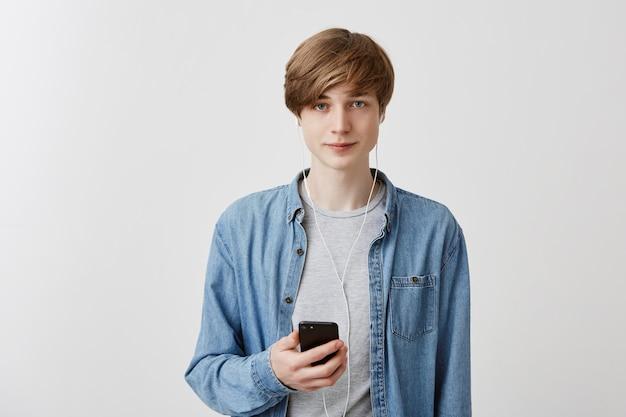 O tiro interno do estudante masculino louro na camisa da sarja de nimes, prende o telefone móvel, conversando com os amigos ou os parceiros, isolados contra a parede cinzenta. cara estiloso navega nas redes sociais, usa conexão wi-fi