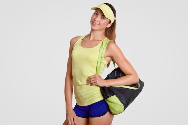 O tiro isolado do jogador de tênis fêmea satisfeito alegre vestido na camiseta e no short ocasionais, prende o saco com equipamento de esporte, continua trainging no gym, está interno. conceito de pessoas e estilo de vida