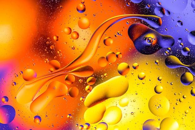 O tiro macro do óleo borbulha com água no fundo colorido.