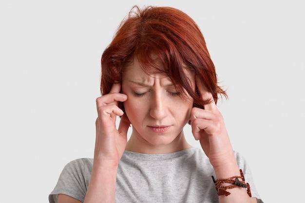 O tiro na cabeça da jovem ruiva estressante mantém os dois dedos indicadores nas têmporas, sofre de enxaqueca, vestida casualmente, isolada no branco, tenta encontrar a solução. headahe conceito