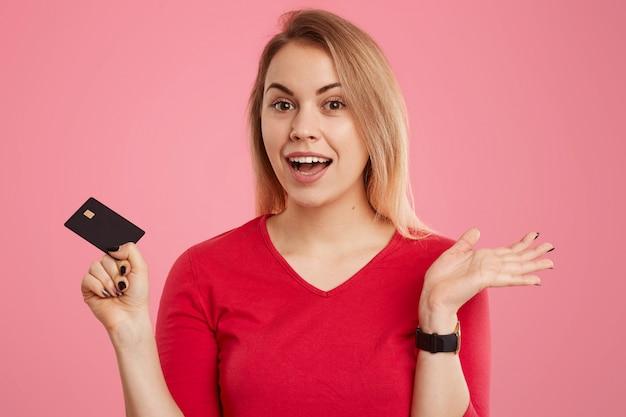 O tiro na cabeça da mulher europeia hesitante positiva de cabelos claros, vestido com jumper vermelho, possui cartão de crédito, tem expressão sem noção, posa em rosa, quer fazer pagamentos ou transações.