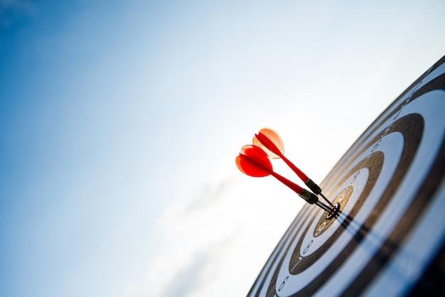 O tiro vermelho arremessa setas no centro do alvo, no alvo do negócio ou no conceito do sucesso do objetivo.