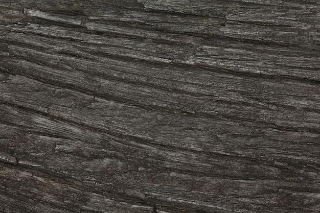 O tom de textura de árvore de madeira real escuro para o fundo padrão