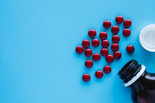 O tônico para o sangue inclui multivitaminas, ácido fólico e líquido de ferro com garrafa em fundo azul para cuidados de saúde e conceito médico