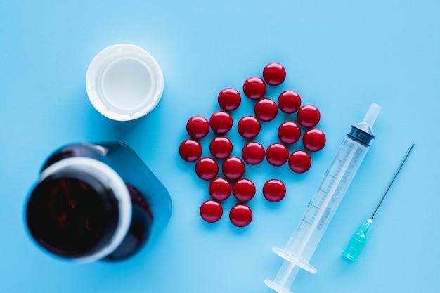 O tônico para o sangue inclui multivitaminas, ácido fólico e líquido de ferro com injeção de garrafa e seringa na superfície azul para cuidados de saúde e conceito médico