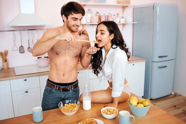 O topless considerável alimenta a jovem mulher com leite e flocos de milho. ela senta na mesa e mantém a boca aberta. casal na cozinha.