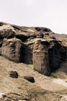 O topo das montanhas rochosas na islândia, o sopé da montanha é coberto com grama amarela