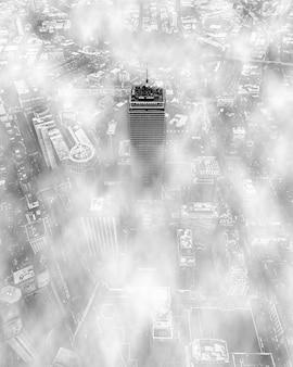 O topo de um arranha-céu cercado por nuvens
