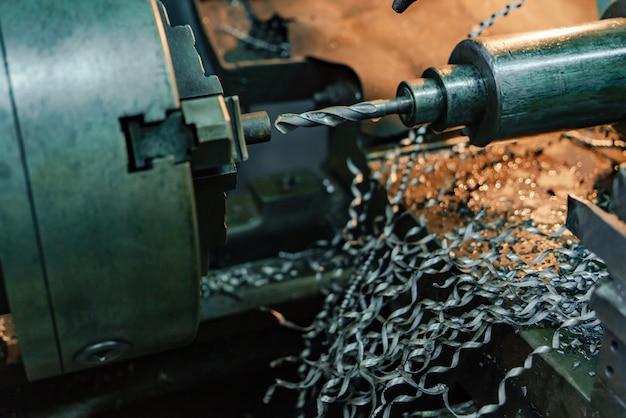 O torno afia a peça e remove as lascas de metal na fábrica.