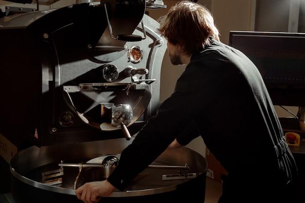 O torrador de café confiante está verificando o processo de preparação