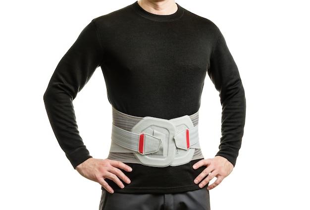 O torso de um homem com um espartilho ortopédico em uma parede branca.