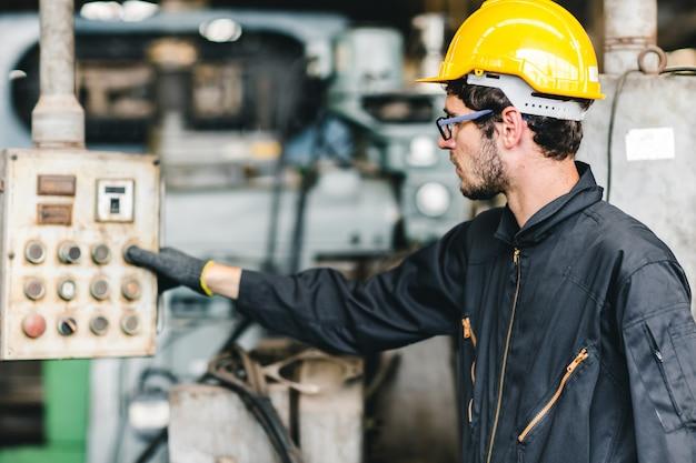 O trabalhador americano novo pretende trabalhar em uma fábrica industrial pesada. controle a máquina pressione o botão