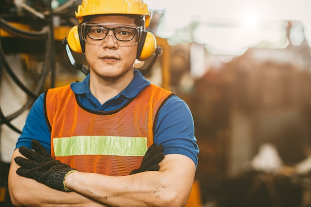 O trabalhador asiático do coordenador que veste as orelhas das capas protetoras para as orelhas protege o ruído e o terno de segurança que trabalham no retrato da fábrica.