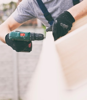 O trabalhador carpinteiro transando com a prancha no telhado