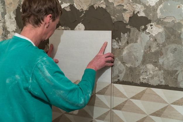 O trabalhador coloca ladrilhos na parede. obras de acabamento, foco desfocado. a tecnologia de colocação de azulejos.