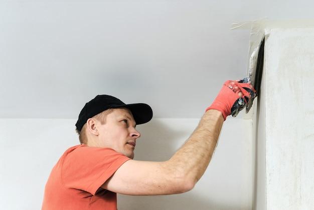 O trabalhador coloca o estuque na parede