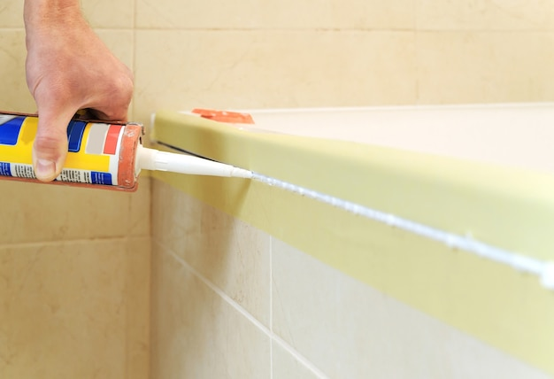 O trabalhador coloca selante de silicone para calafetar a junta entre a banheira e a parede.