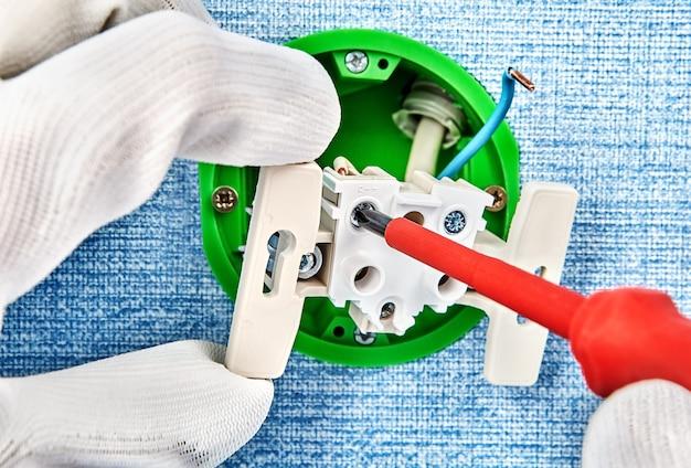 O trabalhador com luvas de proteção está montando a caixa elétrica e girando o parafuso com uma chave de fenda.