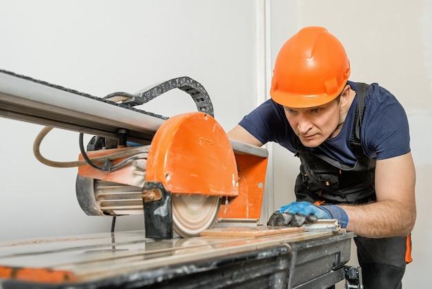 O trabalhador cortando uma telha cerâmica em uma máquina de serra de corte úmido