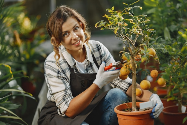 O trabalhador cuida de vasos de flores. menina com uma camisa branca. mulher de luvas