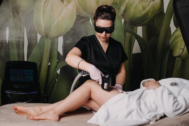 O trabalhador cuidadoso do spa está fazendo uma sessão de depilação nas pernas do cliente enquanto trabalha com aparelhos e óculos modernos