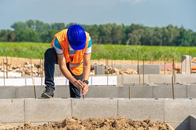 O trabalhador da construção civil constrói a base do edifício.
