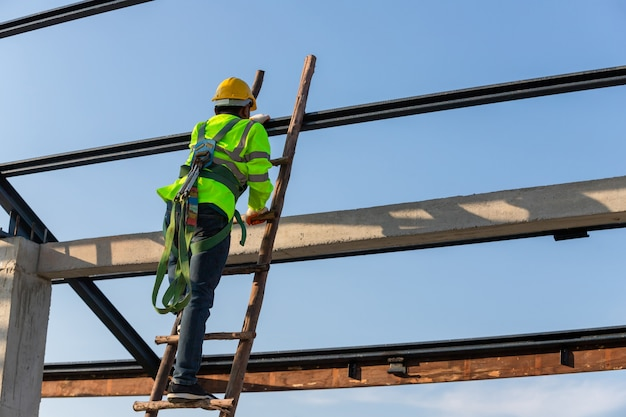 O trabalhador da construção civil de telhado asiático usa equipamento de segurança de altura subindo as escadas para instalar a estrutura do telhado. dispositivo antiqueda para trabalhador com ganchos para cinto de segurança no local de construção