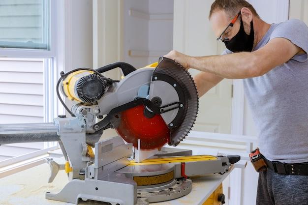 O trabalhador da construção civil usando uma máscara médica para impedir o covid-19 trabalha na remodelação de carpinteiros domésticos que cortam a moldagem de madeira com serra circular.